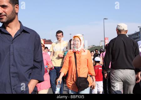 Istanbul Turkey busy street scene with Turkish woman wearing Muslim headscarf among men at Eminonu - Stock Photo