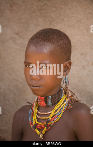 Young girl in traditional dress at the Hamar market in Turmi, Southern Ethiopia, Africa - Stock Photo