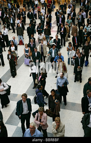 A crowd of people waiting in front of the timetable in Liverpool street station for a train - Stock Photo