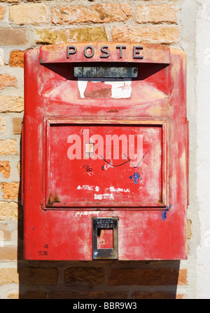 Old red Italian mail box on a wall - Stock Photo