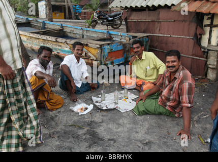 A Group of Keralan men sitting by their fishing boat on a beach in Alleppey - Stock Photo