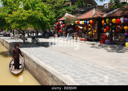 Old Vietnamese man standing in boat next to colorful lantern stalls, 'Hoi An', Vietnam - Stock Photo