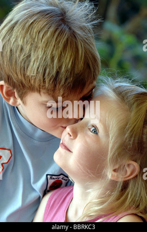 A seven year old boy kisses his five year old sister. - Stock Photo