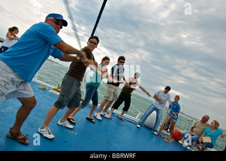 Volunteers in motion blur pulling on rope to help the crew to hoist the main sail aboard sunset cruise catamaran - Stock Photo