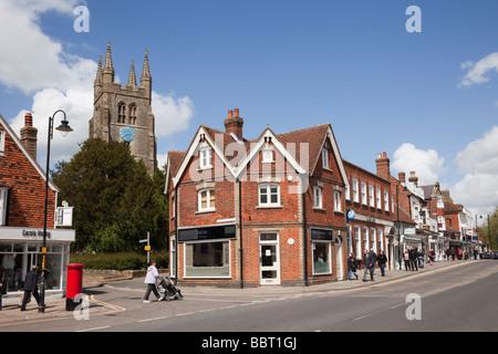 St Mildred's Parish Church clock tower behind shops on High Street in historic Wealden town. Tenterden Kent England - Stock Photo