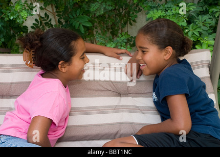 multi racial diversity racially diverse multicultural cTwo sisters 6-7 8-9 year old talking  converse chat chatting - Stock Photo