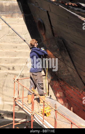 A boat being repaired in dry dock, Gloucester Quays, Gloucestershire - Stock Photo