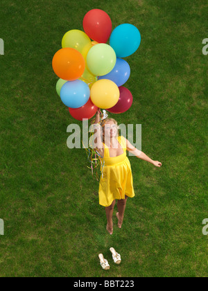 Young happy woman flying up from the ground on colorful air balloons - Stock Photo