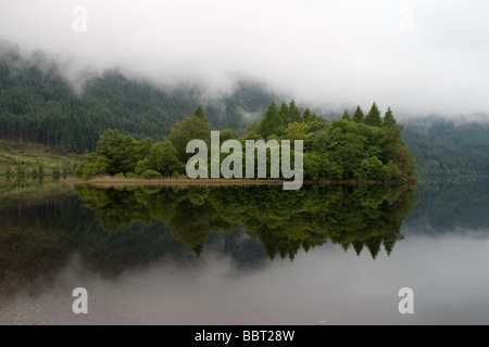 A tree covered island on Loch Chon, Scotland reflected in the calm water - Stock Photo