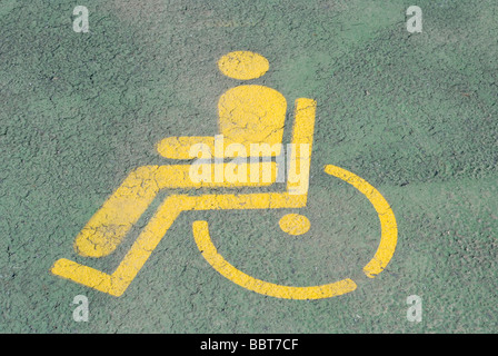 Painted yellow Handicap symbol on a parking space - Stock Photo