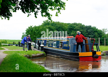 The crew of a barge negotiate one of the gates at Tyrley Locks on the Shropshire Union Canal - Stock Photo