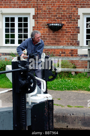 Lock keeper opening one of the Tyrley Lock gates - Stock Photo