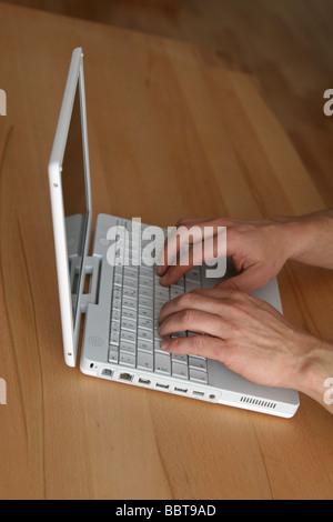 Typing on a notebook - Auf Notebook schreiben - Stock Photo