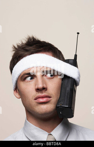 Young man with retro mobile phone - Stock Photo