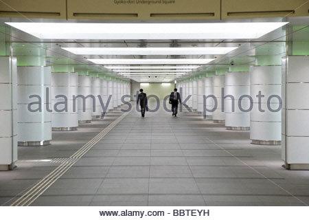businessmen walking in opposite direction through an corridor - Stock Photo