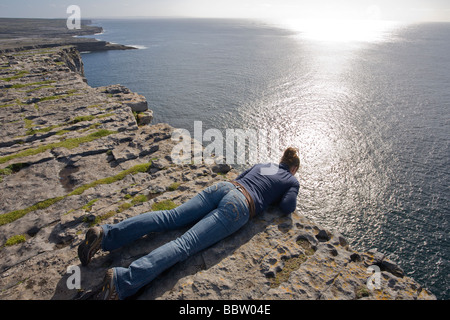 At the Edge. A young woman, echoing the lines in the rock, leans over the 100 meter cliff at Dun Angus to take in - Stock Photo