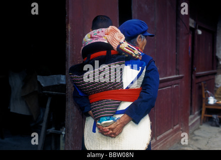 Chinese woman, Naxi woman, grandmother, carrying baby on back, grandchild, ethnic minority, Old Town, Lijiang, Yunnan - Stock Photo