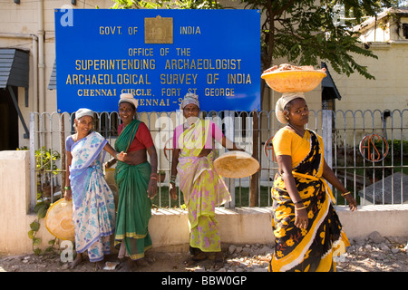 Women shift stones in buckets on their heads within Fort St George, in Chennai, India. - Stock Photo