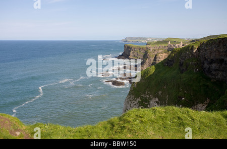 Dunluce and the Antrim  Coastline. The ruin of Dunluce castle clings to the green clad cliffs of the beautiful Antrim - Stock Photo