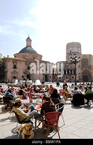 People sitting in cafe terrace in front of the cathedral on Plaza de la Virgen in central Valencia Spain - Stock Photo