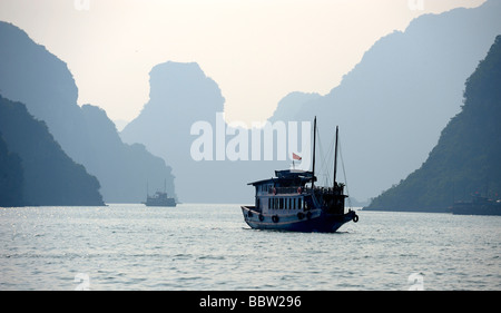 Ship in front of rock formations, Halong Bay, Hanoi, Southeast Asia - Stock Photo