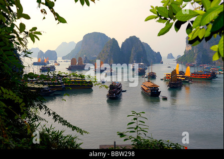 Ships in front of rock formations, Halong Bay, Hanoi, Southeast Asia - Stock Photo