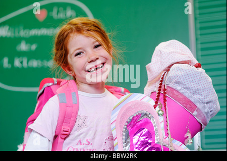 Girl on her first day at school holding a schultuete, school cone filled with sweets and gifts - Stock Photo