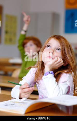 Children in a classroom in primary school, girl daydreaming or looking unsure, thoughtful, sad or frustrated, equal - Stock Photo