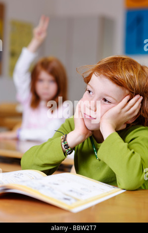 Children in a classroom in primary school, boy daydreaming or looking unsure, thoughtful, sad or frustrated, boys - Stock Photo