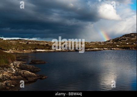 Rainbow over east coatline and loch, Isle of Harris, Outer Hebrides, Scotland - Stock Photo