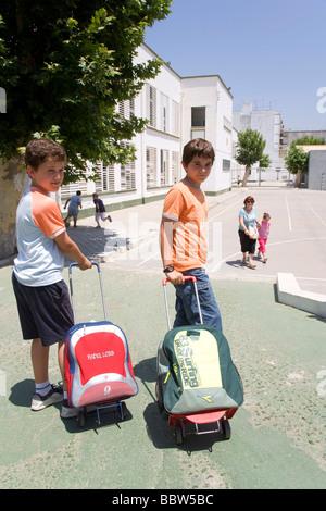 School children leaving Salesiano Satisima Trinidad Primary School, Seville, Andalusia, Spain, Europe - Stock Photo