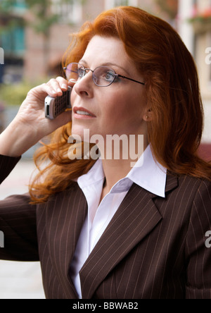 Professional businesswoman with red hair and glasses talking on her mobile phone - Stock Photo