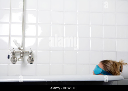 young woman in bathtub wearing an eye mask - Stock Photo
