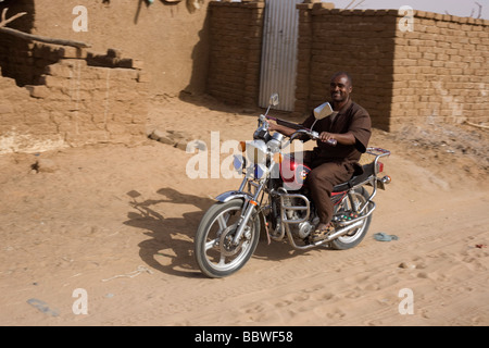 Man on a smart motorbike smiles as he rides past the viewer in the 4 sq km Abu Shouk refugee camp in Al Fasher, - Stock Photo