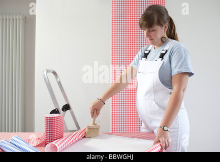 Pregnant woman is paperhanging - Stock Photo