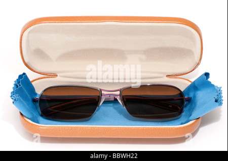 Pair of brown polaroid prescription mans sunglasses and blue spectacle microfibre cloth lens cleaner in a beige - Stock Photo