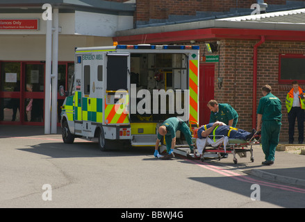 Ambulance Crew Offloading a Patient at The Emergency Department East Surrey NHS Hospital Redhill England - Stock Photo