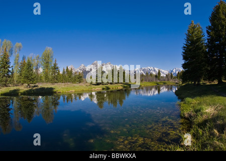 Reflections in lake of snow covered mountains in Grand Teton National Park in Wyoming - Stock Photo