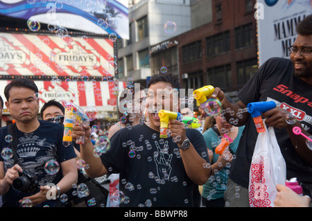 Hundreds of people gather in Times Square in New York to launch millions of bubbles - Stock Photo