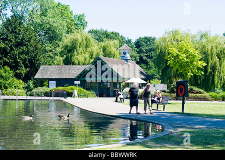 London , Regent's Park , peaceful scene of childrens' boating lake with two Canadian geese & cafe restaurant in - Stock Photo