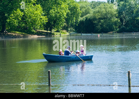 London , Regent's Park , family , father , mother & two daughter in blue rowing boat on lake in spring sunshine - Stock Photo