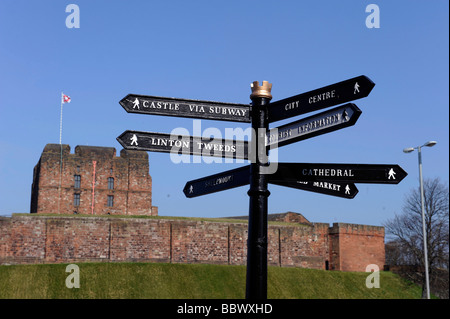 Tourist signpost with Carlisle castle in background - Stock Photo