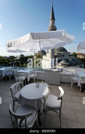 Table and sun shade on the roof terrace of a small hotel in Sultanahmet, view to Firuz Aga Mosque and Blue Mosque, - Stock Photo