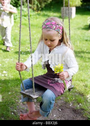 A girl in a swing Skane Sweden. - Stock Photo
