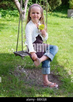 A smiling girl sitting in a swing Skane Sweden. - Stock Photo