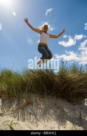 A young woman jumping Skane Sweden. - Stock Photo