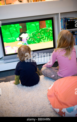 Two children looking at a cartoon on the television Sweden. - Stock Photo
