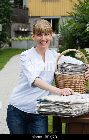 A woman recycling newspapers Sweden. - Stock Photo