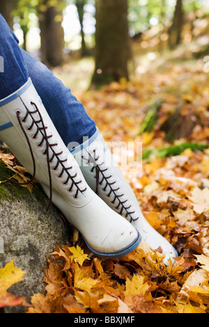 A woman wearing rubber boats in autumn forest Stockholm Sweden. - Stock Photo