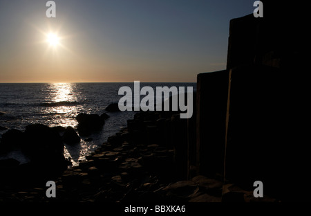 sun shining on giants causeway county antrim coast northern ireland uk europe - Stock Photo